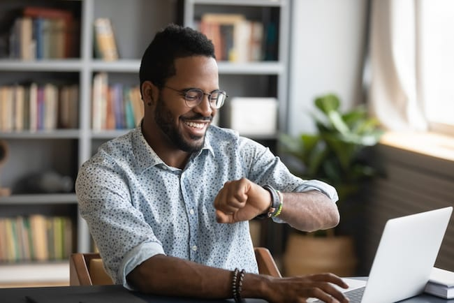 Man working from home looks at his watch