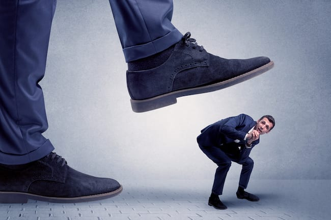 young businessman getting crushed by giant shoe