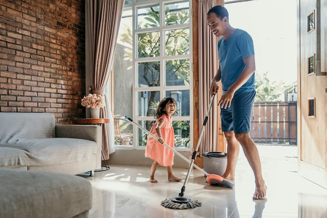 man mops floor with young daughter