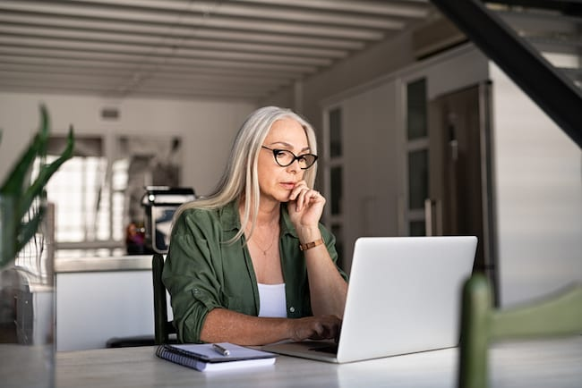 Woman tries to focus on work in front of her laptop