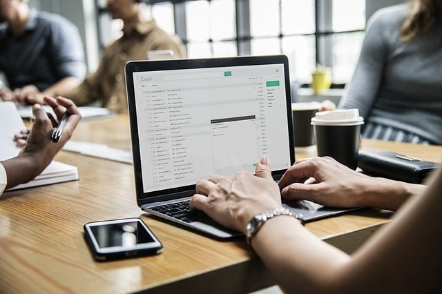 worker at conference table checks email on computer