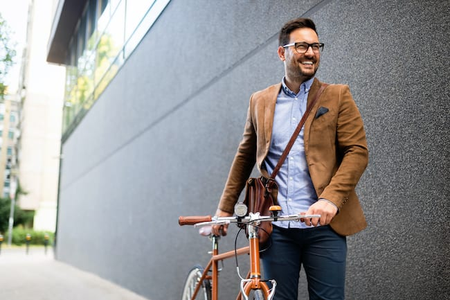 a man dressed for work walks beside his bicycle. Exercise can improve the ability to focus in the workplace
